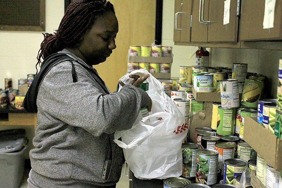 Loading a bag, senior Tal'itha Clinton fills an order in the food pantry. The food pantry offers students the chance to place orders twice a week.