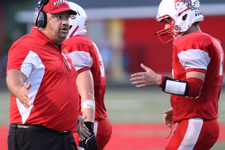 Coach Jay Lee congratulates Red Devil players as they come off the field during a game last fall. Lee resigned on January 25.