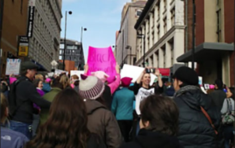 Walking down the street, men and women hold signs up protesting for women's rights. The women's march took place in Cincinnati.