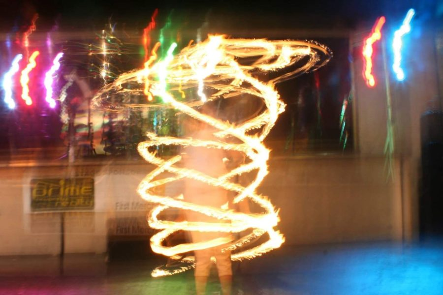 Exceptional education teacher Archer Bunner hula hooping with fire during a performance.