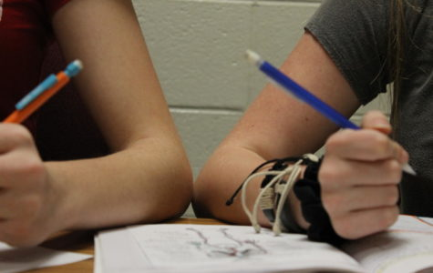 Two students, one left-handed and the other right-handed bumping elbows when trying to do their work