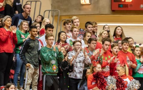 Wearing Christmas sweaters, the student section cheers on the basketball team.