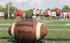 Out of focus, the football team practices on the field.