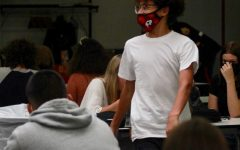 An RHS student walks in the cafeteria wearing a mask.