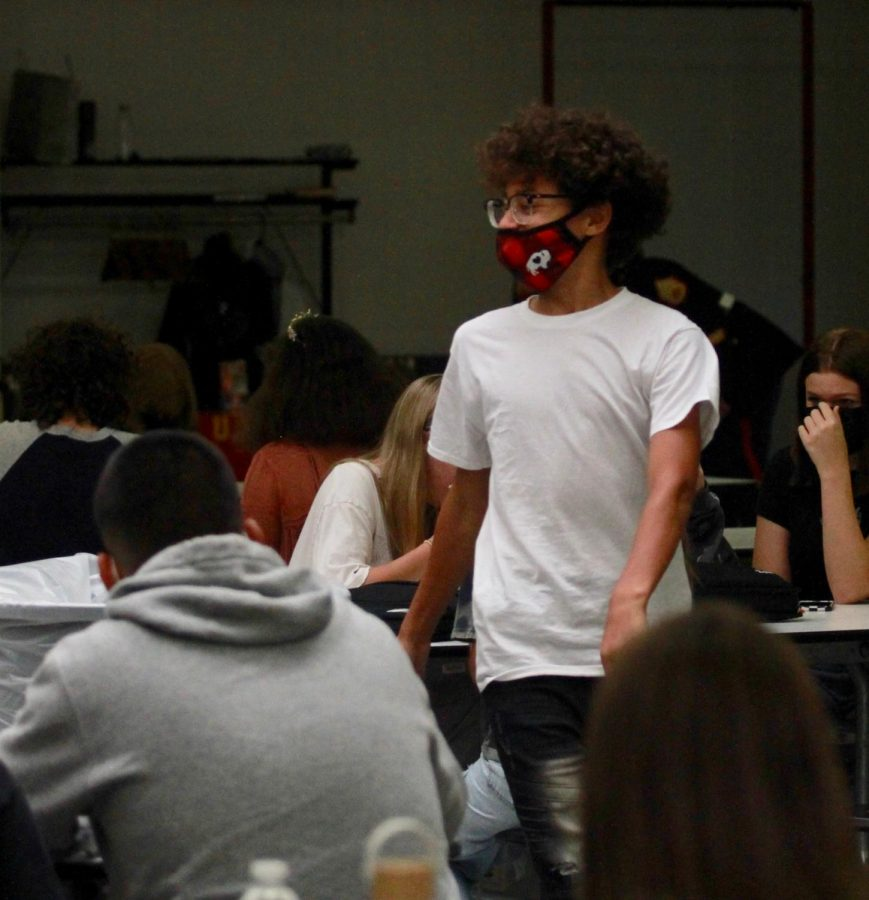 An+RHS+student+walks+in+the+cafeteria+wearing+a+mask.